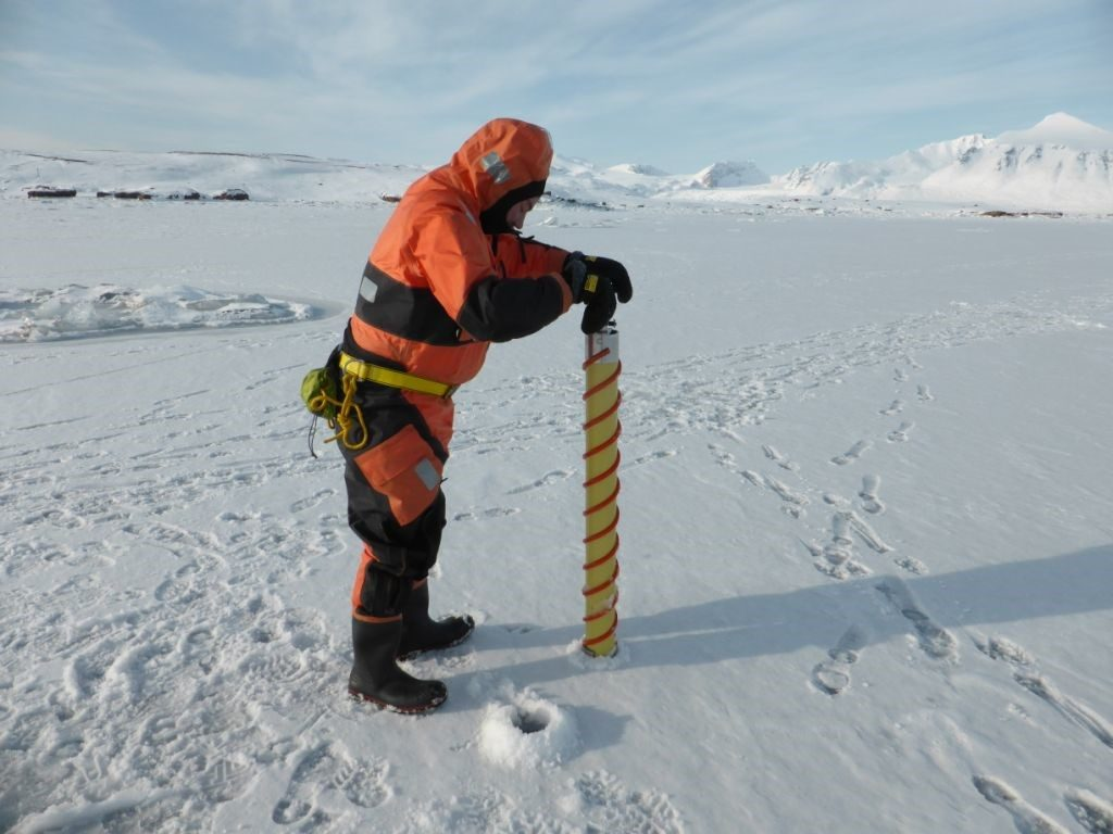 Figure 7. Conducting in situ sea ice measurements and sampling on one of the stations in Kongsfjorden (Photo: S. Gerland).